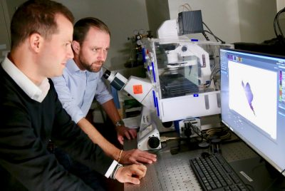 Picture of Daniel Slade on the left and Scott Verbridge on the right, in front of a computer in a lab.
