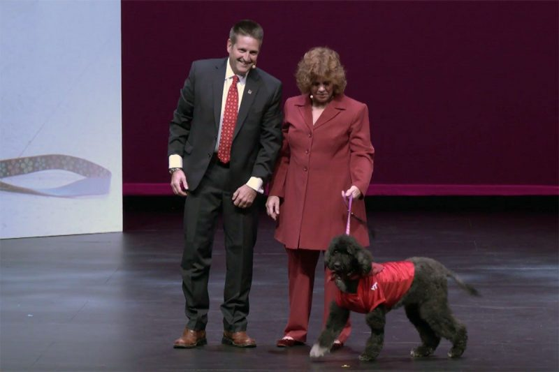 John Rossmeisl and Laura Kamienski with her dog, Emily, on stage at the campaign kickoff event at the Moss Arts Center