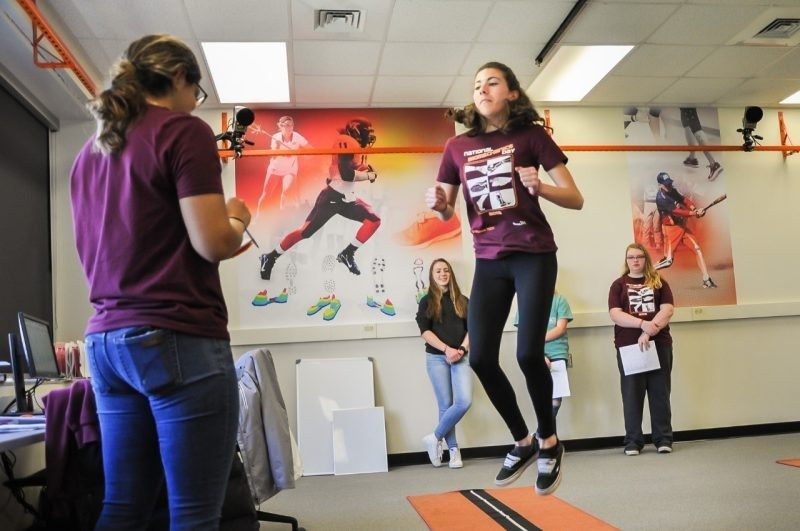 A photo of a high school student performing a vertical jump test in the Granata Lab as part of National Biomechanics Day activities.