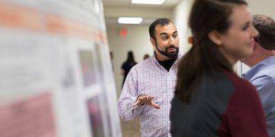 A BEAM graduate student explains his research findings to several onlookers during a presentation