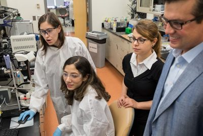 A group of BEAM grad students and faculty observe the results of an experiment in the lab