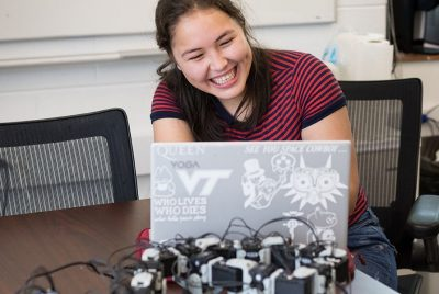 A BEAM undergrad laughs as she works at her laptop, modifying the programming of her robot.