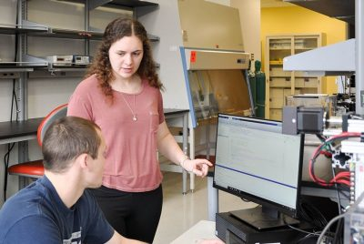 Two BEAM undergraduate students discuss the data displayed on their lab station's computer monitor