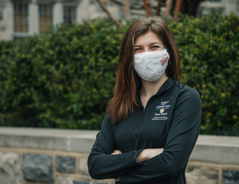 Nicole Stark, doctoral student in biomedical engineering and mechanics, stands in front of green bushes on Virginia Tech campus, wearing a black VT pullover and a mask.